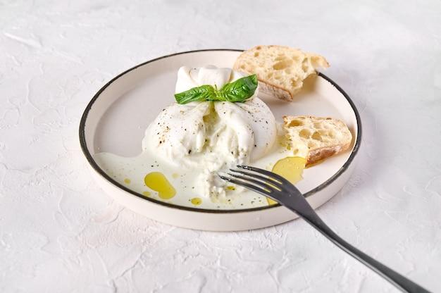 Italiaanse gesneden burrata-kaas met ciabattabrood en olijfolie op witte plaat met zwarte vork close-up
