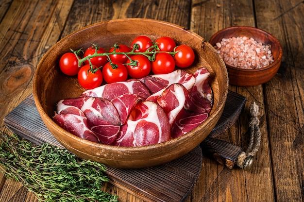 Italiaanse gesneden coppa ham met kruiden. houten achtergrond. bovenaanzicht.