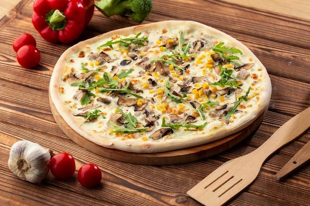 Italiaanse heerlijke vers gebakken pizza met smeltende kaas, gesneden champignons, rucola en suikermaïs op gestructureerde rustieke achtergrond. pizza met champignons. bovenaanzicht.