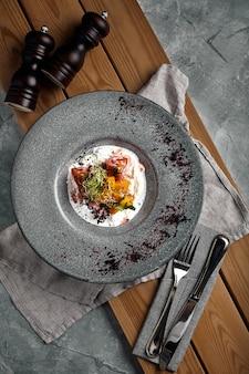 Italiaanse kaas burrata mozzarella en strachatella wordt geserveerd op een schotel met paprika tomaten en verse rucola versgemalen peper en olijfolie selectieve focus donkere achtergrond