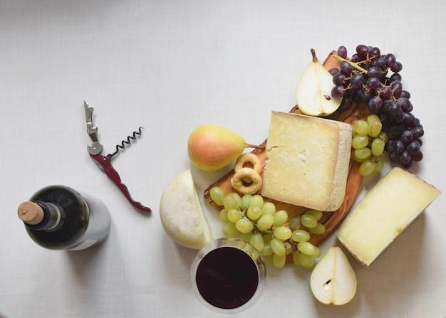 Italiaanse kaas met peren en druiven op houten wit snijplank ,.