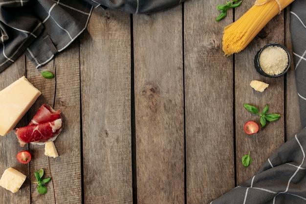 Italiaanse keuken concept plat leggen. parmezaanse kaasblokjes, geraspte kaas in een zwarte kom, rauwe pasta, dungesneden ham