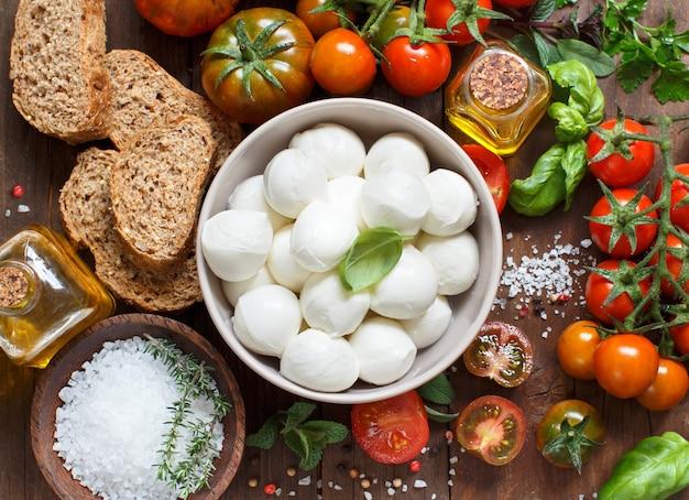 Italiaanse keuken ingrediënten mozzarella, tomaten, basilicum, olijfolie en ander bovenaanzicht