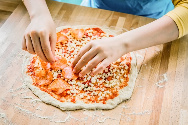 Italiaanse keuken. verse smakelijke pizza voorbereiding. vrouwelijke handen die pepperoni op pizza zetten.