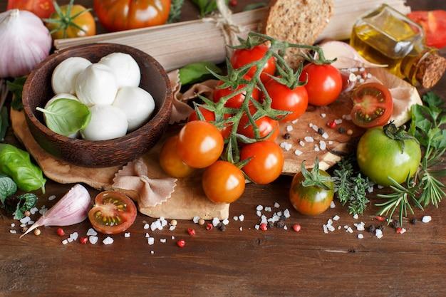 Italiaanse kokende ingrediënten mozzarella, tomaten, basilicum, olijfolie en andere close-up