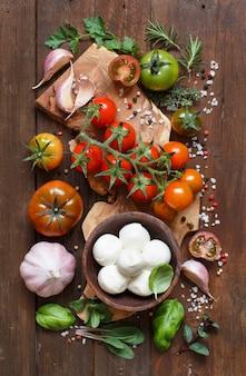 Italiaanse kokende ingrediënten mozzarella, tomaten, knoflook, kruiden en andere op houten tafelblad bekijken