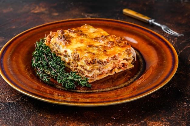 Italiaanse lasagne met tomatensaus bolognesesaus en gehakt rundvlees op een rustieke plaat