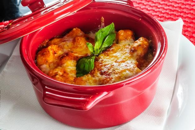 Italiaanse lasagneplaat die met vers basilicumblad wordt gediend