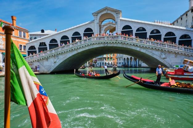 Italiaanse maritieme vlag met rialto-brug met gondels in bacground. grand canal, venetië, italië