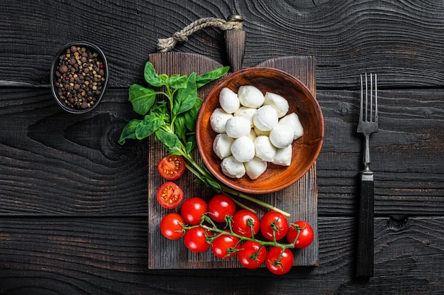 Italiaanse mini mozzarella-kaasballetjes, basilicum en tomatenkers klaar voor het koken van caprese-salade. zwarte houten achtergrond. bovenaanzicht.