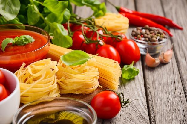 Italiaanse mozzarella, tomaten, basilicum en olijfolie van voedselingrediënten op rustieke houten achtergrond.