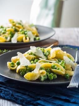 Italiaanse orecchiette pasta met erwten en kaas
