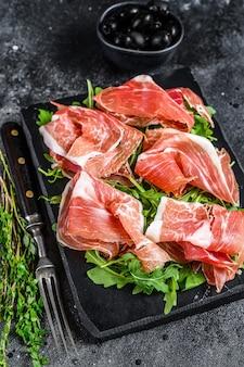 Italiaanse parma prosciutto crudo gedroogde ham op een marmeren bord. zwarte achtergrond. bovenaanzicht.