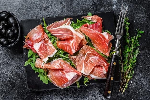 Italiaanse parma prosciutto crudo gedroogde ham op een marmeren bord.