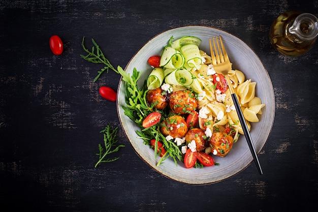 Italiaanse pasta. conchiglie met gehaktballen, fetakaas en salade op donkere tafel. diner. bovenaanzicht, boven het hoofd. slow food concept