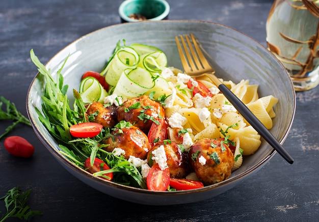 Italiaanse pasta. conchiglie met gehaktballen, fetakaas en salade op donkere tafel. diner. slow food concept