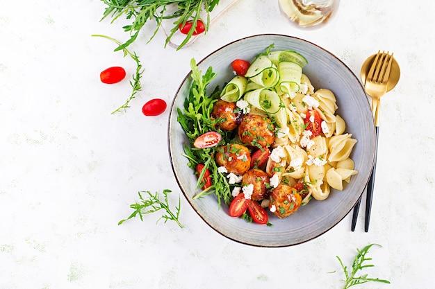 Italiaanse pasta. conchiglie met gehaktballen, fetakaas en salade op lichte tafel. diner. bovenaanzicht, boven het hoofd. slow food concept