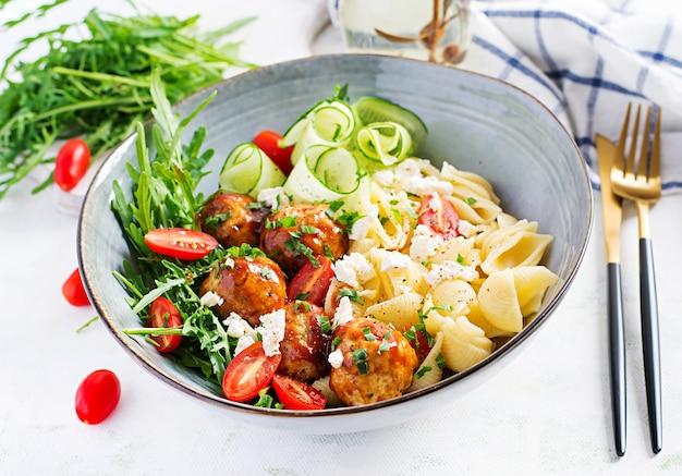 Italiaanse pasta. conchiglie met gehaktballen, fetakaas en salade op lichte tafel. diner. slow food concept