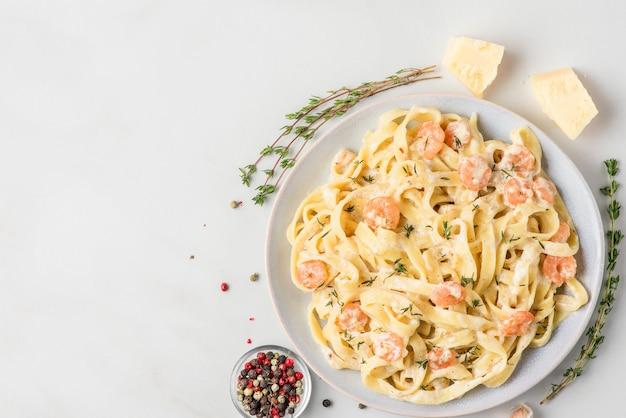 Italiaanse pasta fettuccine met garnalen in een romige saus met parmezaanse kaas en tijm op een bord