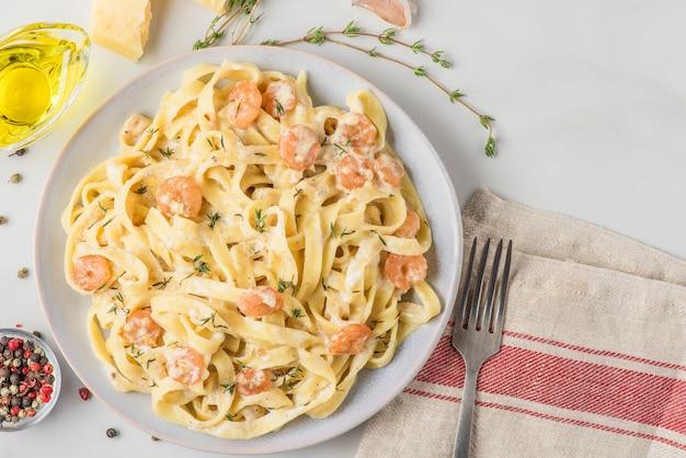 Italiaanse pasta fettuccine of tagliatelle met garnalen in een romige saus met parmezaanse kaas en tijm op een bord