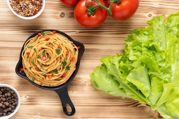 Italiaanse pasta in een koekenpan op een houten achtergrond. bovenaanzicht.
