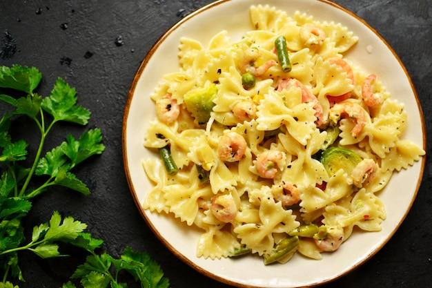 Italiaanse pasta in een romige saus met garnalen op een plaat, bovenaanzicht. farfalle met garnalen op een donkere tafel.