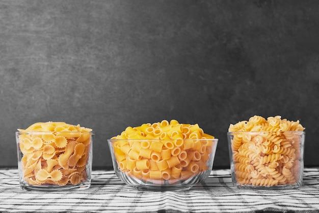Italiaanse pasta in glazen bekers op zwarte achtergrond