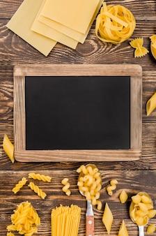 Italiaanse pasta in lepels met schoolbord
