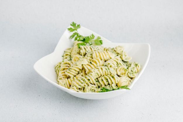 Italiaanse pasta met groene kruiden in een witte kom.