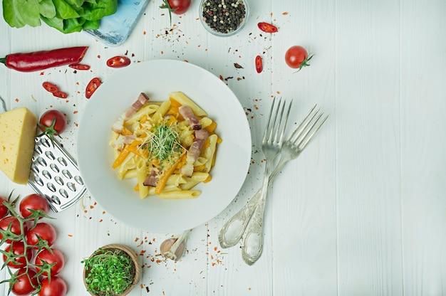 Italiaanse pasta met kaas, pompoen en gebakken spek, geserveerd op een wit bord. lichte houten achtergrond. ruimte voor tekst.
