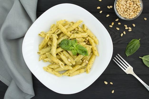 Italiaanse pasta met pesto en pijnboompitten in de witte plaat op de zwarte houten tafel