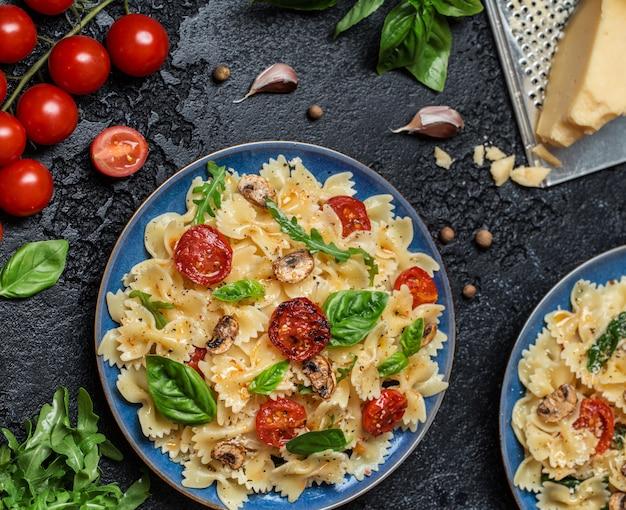 Italiaanse pasta met saus, cherrytomaatjes, basilicum en parmezaanse kaas. heerlijke pasta plaat