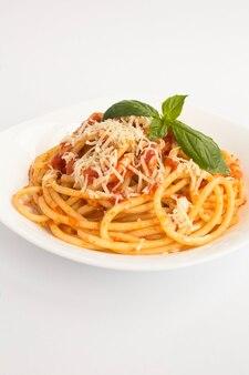 Italiaanse pasta met tomatensaus en parmezaanse kaas in de plaat op de witte achtergrond. ruimte kopiëren. locatie verticaal.