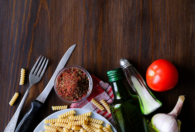 Italiaanse pasta, olijfolie, specerijen op een donkere houten tafel