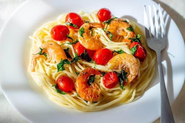 Italiaanse pasta spaghetti met garnalen en tomaten. nationale keuken.