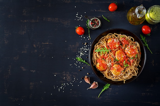 Italiaanse pasta. spaghetti met gehaktballen en parmezaanse kaas in zwarte plaat