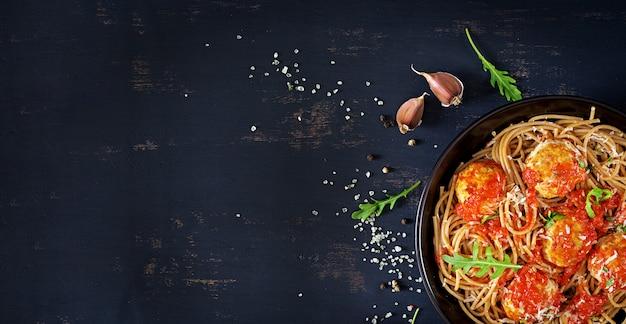 Italiaanse pasta. spaghetti met vleesballetjes en parmezaanse kaaskaas in zwarte plaat op donkere rustieke houten achtergrond. avondeten. bovenaanzicht banner. slow food concept