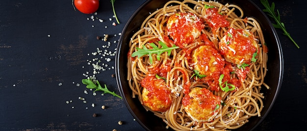 Italiaanse pasta. spaghetti met vleesballetjes en parmezaanse kaaskaas in zwarte plaat op donkere rustieke houten achtergrond. avondeten. bovenaanzicht slow food concept