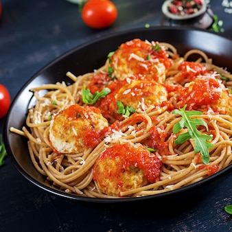 Italiaanse pasta. spaghetti met vleesballetjes en parmezaanse kaaskaas in zwarte plaat op donkere rustieke houten achtergrond. avondeten. slow food concept
