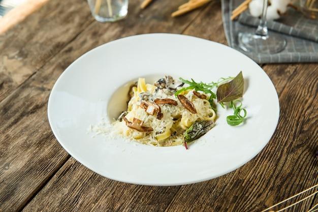 Italiaanse pasta tagliatelle alfredo met champignons