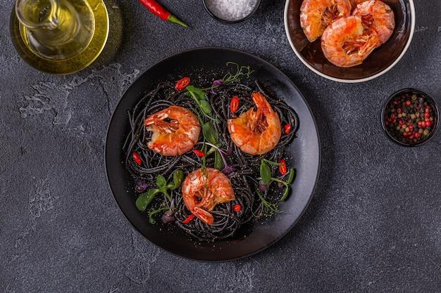 Italiaanse pasta zwarte spaghetti met garnalen en microgreens, bovenaanzicht.