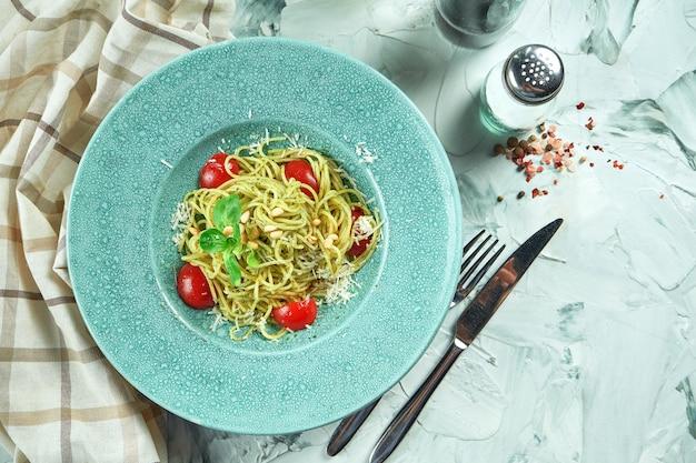 Italiaanse pastaspaghetti met pestosaus en tomaten in een blauw bord in een compositie met keukengerei
