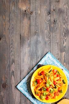 Italiaanse penne pasta in tomatensaus en verschillende soorten groenten,