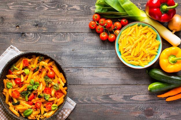 Italiaanse penne pasta in tomatensaus en verschillende soorten groenten