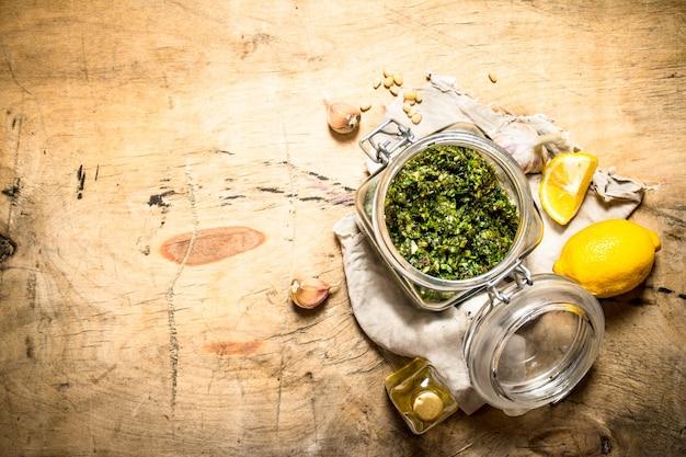 Italiaanse pesto met citroen, pijnboompitten en andere ingrediënten. op een houten tafel