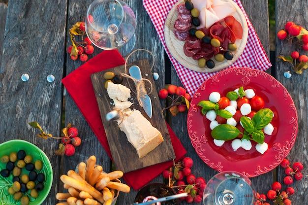 Italiaanse picknick met rode wijn, parmezaanse kaas, ham, caprese salade en olijven. lunch in de open lucht en houten tafel. traditionele snacks. kopieer ruimte