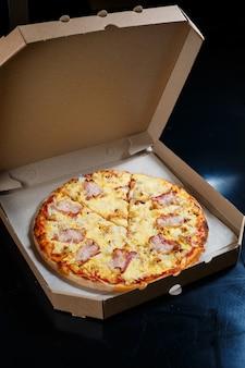 Italiaanse pizza bezorgen. heerlijke ovengebakken pizzeriaschotel met mozzarella, parmezaan en kaas, geleverd in een kartonnen doos. heerlijke afhaalmaaltijden fastfood gekookt in de oven voor het diner.