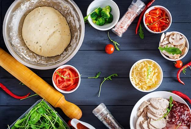 Italiaanse pizza. deeg en pizza ingrediënten. deeg, kaas, tomaten, broccoli, champignons, salami, ham, kipfilet of bakkerij koken. bovenaanzicht
