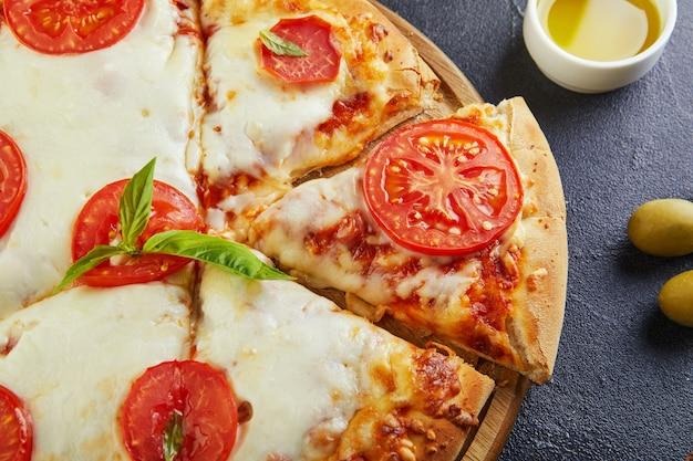 Italiaanse pizza en ingrediënten voor het koken op een zwarte betonnen achtergrond. tomaten, olijven, basilicum en kruiden. gesneden driehoek van pizza. kopieer ruimte voor tekst. plat liggen
