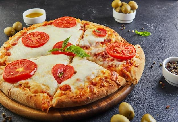Italiaanse pizza en ingrediënten voor het koken op een zwarte betonnen zijaanzicht als achtergrond